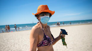 A woman wearing a sunhat and protective face mask walks along the 'Couchant or Sunset beach' in La Grande Motte, southern France, on May 21, 2020,