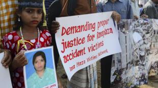 Cette jeune fille porte la photo de sa mère décédée lors du drame du Rana Plaza, ce dimanche 24 avril à Dacca.