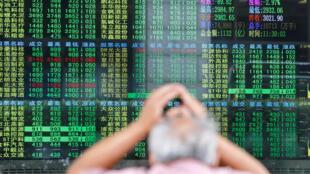 一名男子透过窗户看一家经纪公司的股票电子资讯看板  2018年6月19日上海