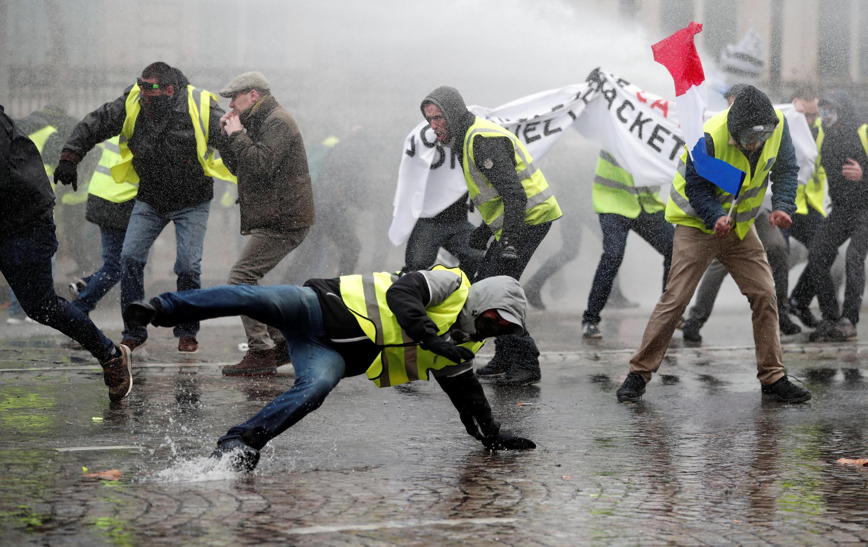 Les manifestants fuient dans les rues adjacentes ou reculent face aux jets des puissants canons à eau, toujours sur l'Avenue des Champs-Élysées.