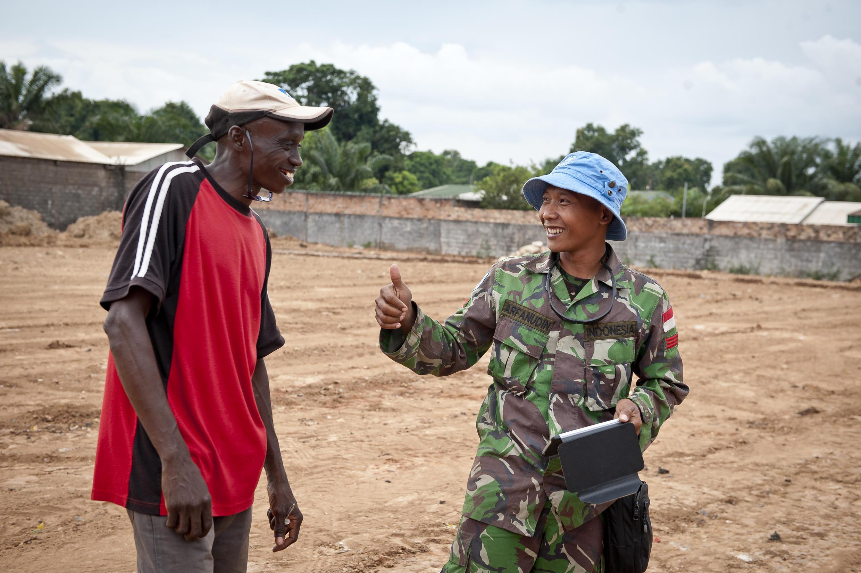 Un casque bleu indonésien de la Minusca, qui se déployera en septembre, échange avec un civil à Bangui. 12 juin 2014..