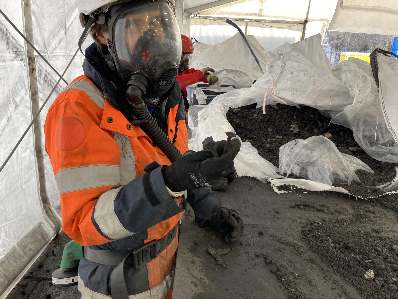 La arqueóloga Dorothy Choi-Tereux extrae un clavo falso de una ruina construida a mano.  Luego será revisado por expertos (febrero de 2021).