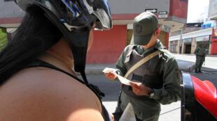 Un funcionario venezolano controla los documentos de la gente en San Antonio, Táchira.