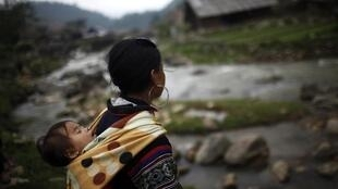 A Hmong woman walks along a river in northern Lao Cai province, Vietnam.