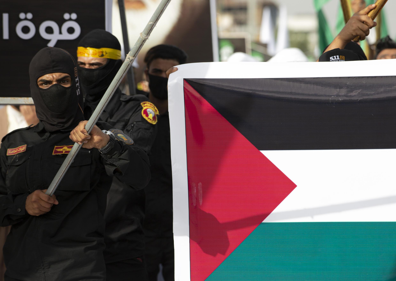 Miembros del grupo paramilitar chiíta proiraní Al-Hashd Al-Shaabi portan una bandera palestina durante un mitin por el Día Internacional de Al Quds (Jerusalén), en la ciudad de Basora, Irak, el 7 de mayo de 2021