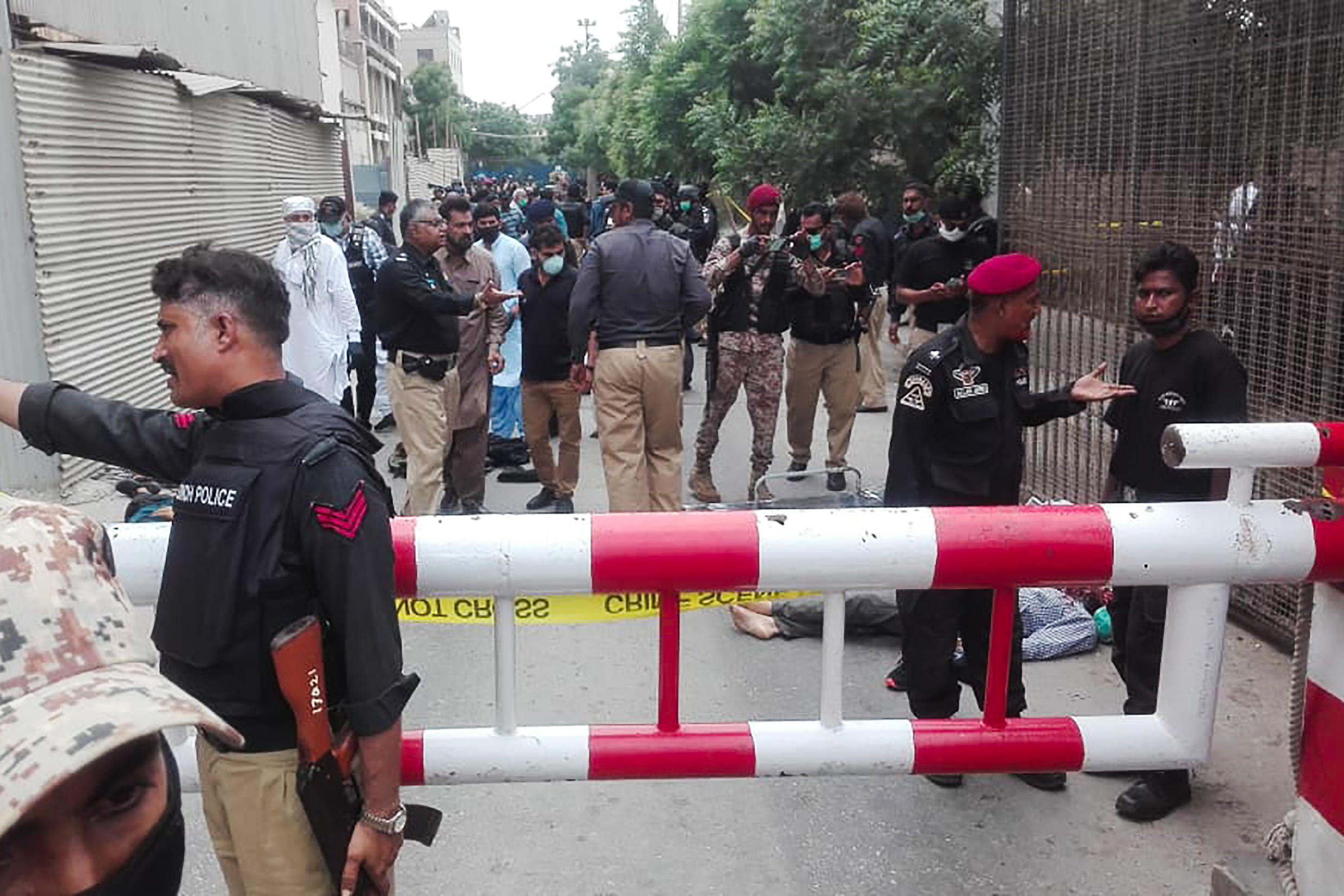 Policemen secure an area around a body outside the Pakistan Stock Exchange building after a group of gunmen attacked the building in Karachi