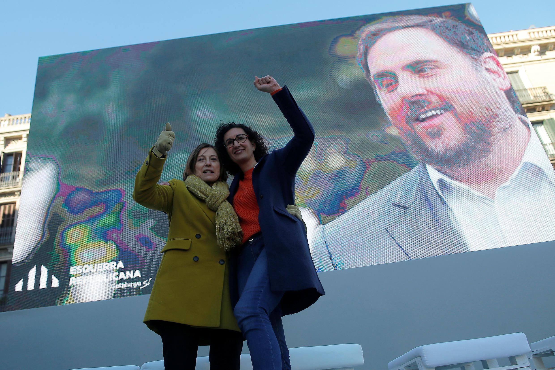 Лидеры списка «Левые республиканцы Каталонии» Марта Ровира (справа) и Карме Форкадел на фоне портрета арестованного лидера партии Ориола Жункераса в Барселоне.