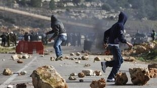 Palestinian youths throw stones towards Israeli security officers during clashes