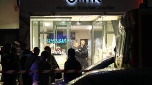 Des policiers sont postés à l'entrée de la bijouterie où un homme a été tué lors du braquage par quatre malfaiteurs de son établissement, le 26 novembre 2011 à Cannes, dans le sud de la France.