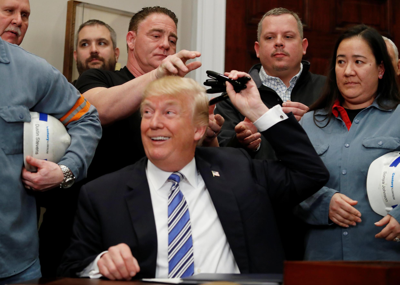 Le président Trump en compagnie d'ouvriers mettalurgiques après qu'il ait promulgué de nouvelles taxes sur l'importatation d'acier et d'aluminium le 8 mars 2018.