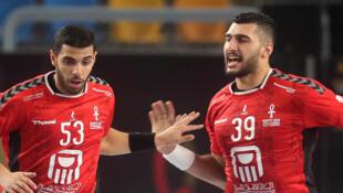 L'arrière gauche égyptien Yehia Elderas (d) célèbre son but avec l'ailier droit Akram Saad, lors du match d'ouverture du Mondial de handball contre le Chili, le 13 janvier 2021 au Caire