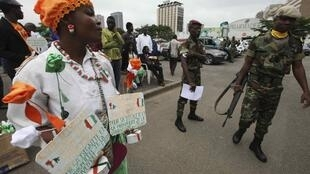 A street vendor sells souvenirs during the 51st Ivorian independence day ceremony in Abidjan