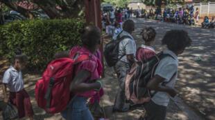 Des élèves quittent l'école primaire de Roodeport, où la nomination d'une nouvelle principale a provoqué de vives protestations.