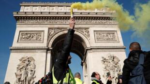 """Manifestante vestindo colete amarelo segura uma tocha de perto do Arco do Triunfo durante uma demonstração do movimento """"coletes amarelos"""" em Paris"""