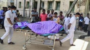 Des employés d'un hôpital sri-lankais transportent un cadavre sur un chariot à la morgue d'un hôpital à la suite d'une explosion survenue dans une église de Batticaloa, dans l'est du Sri Lanka, ce dimanche 21 avril 2019.