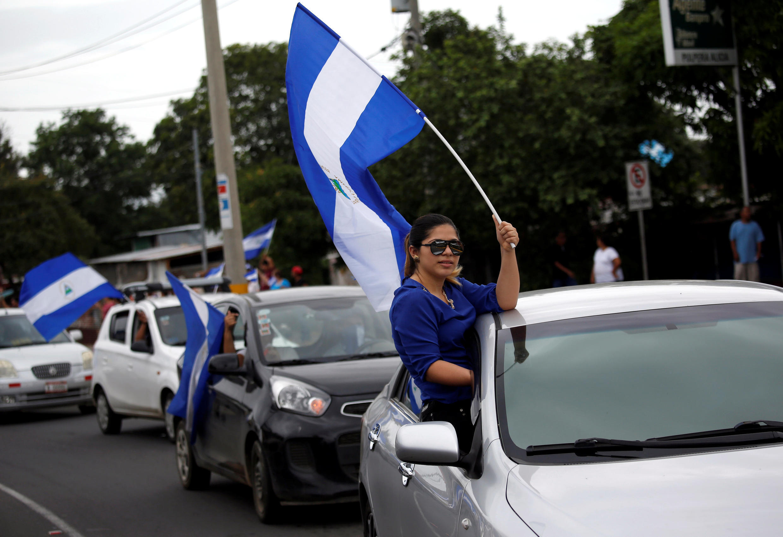 Những người xuống đường vẫy quốc kỳ trong một cuộc biểu tình chống lại chính phủ của tổng thống Daniel Ortega, dọc theo con đường ở Managua, Nicaragua, ngày 10/06/2018.