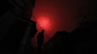 Un homme seul s'avance dans la nuit alors que retentit un feu d'artifice pour la nouvelle année chinoise.