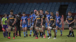 Bulls (blue jerseys) and Stormers players walk off at Loftus Versfeld stadium in Pretoria Saturday after the referee suspended play due to an approaching storm. The match was later called off with the 39-6 lead held by the Bulls declared the result.