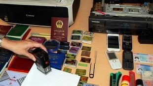A Spanish police officer shows fake passeports and material seized during the operation