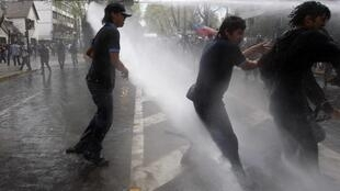 Estudantes chilenos recebem jato de água durante manifestação contra o governo em Santiago, nesta segunda-feira.