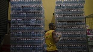 Un manutentionnaire range des packs d'eau minérale dans un magasin d'alcool de Rio de Janeiro, au Brésil, le 15 janvier 2020.