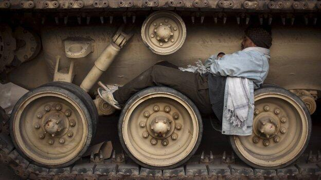Man in Cairo's Tahrir square takes a nap atop the wheels of an army tank