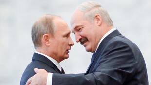 Le président biélorusse Alexander Loukachenko (d) reçoit le président russe Vladimir Poutine pour le sommet de la Communauté des Etats indépendants (CIS), à Minsk, le 10 octobre 2014.