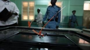 Des employés de la Commission nationale électorale et des policiers soudanais veillent sur les urnes scellées après la fermeture d'un bureau de vote à Khartoum le 15 avril 2010.