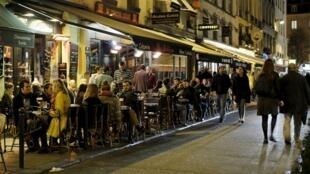 Devant un café parisien. Des milliers d'étrangers, résidant parfois depuis longtemps en France, se passionnent pour l'élection, sans pouvoir y participer.