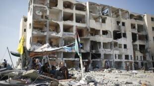 Palestinos em frente de um prédio residencial destruído por bombardeio israelense. 11 de agosto de 2014.
