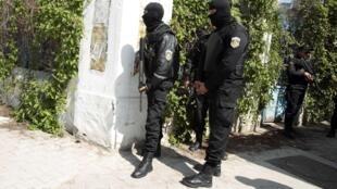 Ces officiers plus lourdement armés et cagoulés se tiennent prêts à intervenir.