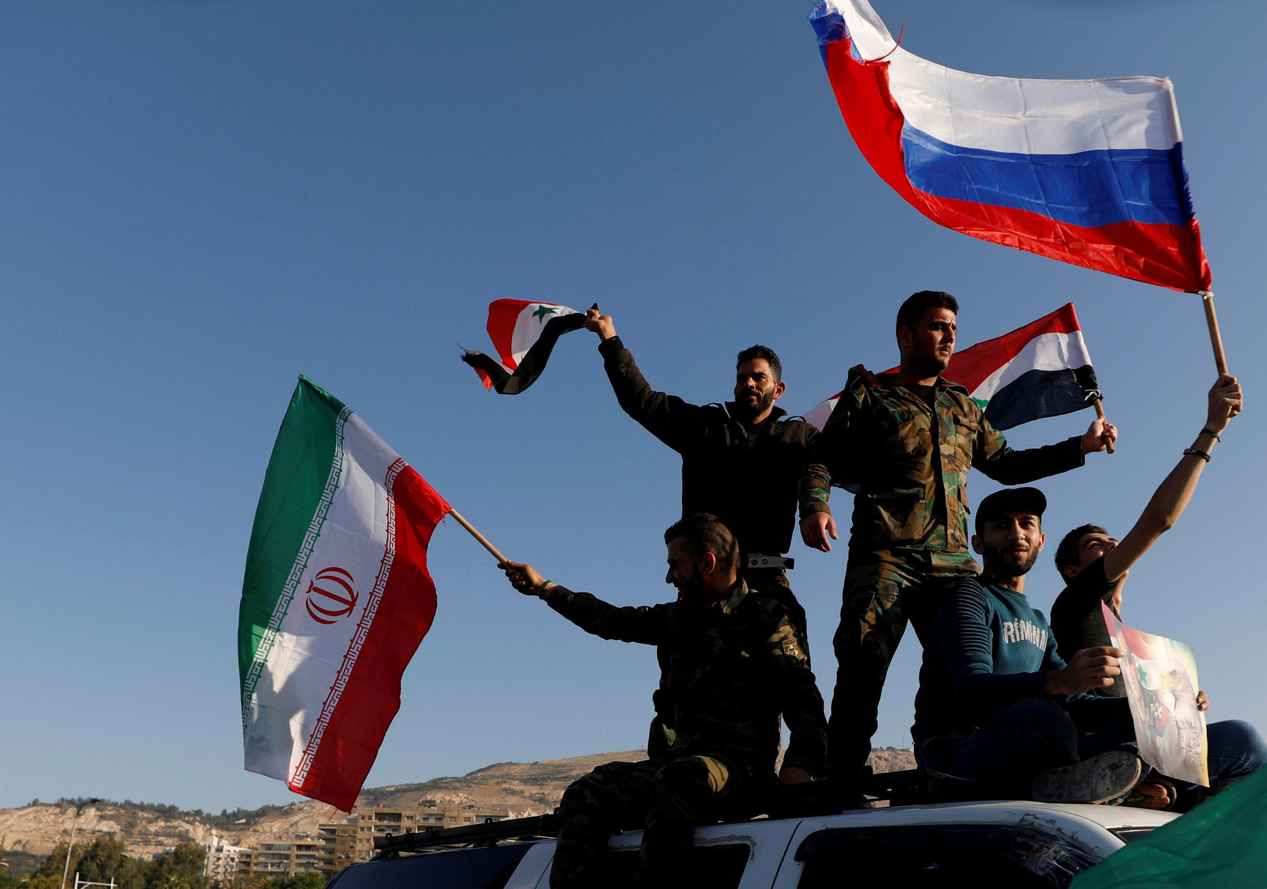 Syrians wave Iranian, Russian and Syrian flags in protest at the US-led air strikes in Damascus