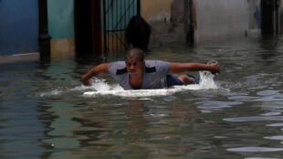 Un hombre utiliza una plancha para cruzar una calle inundada de La Habana, Cuba, el 10 de septiembre de 2017.