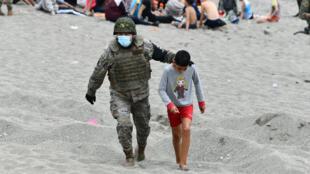 Un soldado español camino con un menor migrante, el 18 de mayo de 2021 en Ceuta