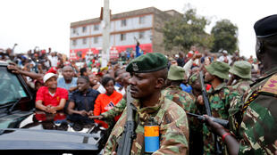 Les forces de l'ordre sont positionnées près du véhicule où se trouve Uhuru Kenyatta pour garantir sa sécurité.
