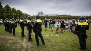 Les forces de l'ordre devant les manifestants à Malieveld, à quelques centaines de mètres du siège du gouvernement à La Haye le 21 juin 2020.
