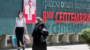 Des personnes portant le masque pour se protéger de l'épidémie de Covid-19 passent devant l'hôpital 8-Septembre de Skopje, le 3 juin 2020.