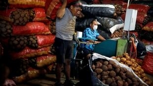 Travailleur portant un sac de patates dans un marché de Lima, le 21 mars 2020. L'économie du pays est à l'arrêt, en raison du coronavirus.