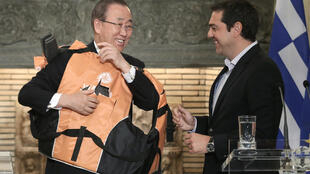 Alexis Tsipras aidant Ban Ki-moon à enfiler un gilet de sauvetage, à Athènes, le 18 juin 2016.