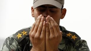 An Egyptian soldier takes part in Friday prayers at Cairo's Tahrir Square, 25 February 2011