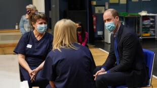 El príncipe Guillermo habla con dos técnicas sanitarias de un centro de vacunación contra el coronavirus de King's Lynn, el 22 de febrero de 2021 al este de Inglaterra