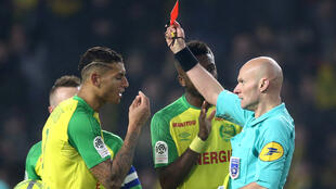 French referee Tony Chapron hands Nantes defender Diego Carlos a red card after kicking him following an accidential collision during the team's Ligue 1 match against Paris Saint-Germain on 14 January 2018.
