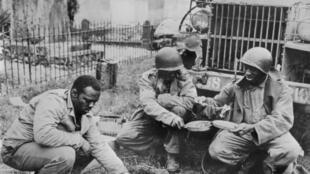 Des soldats américains prennent leur repas près d'un camion de ravitaillement en France peu après le débarquement des troupes US.