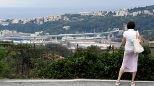 Une passante regarde, le pont San Giorgio, le nouveau pont de Gênes qui remplace celui qui s'est effondré le 14 août 2018 tuant 43 personnes, peu avant son inauguration le 3 août 2020.