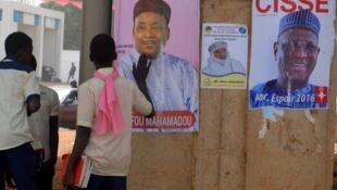 Des étudiants passent devant les affiches électorales des candidats Mahamadou Issoufou, président sortant, et Amadou Boubacar Cissé, ancien ministre (à droite), à Niamey, le 30 janvier 2016.
