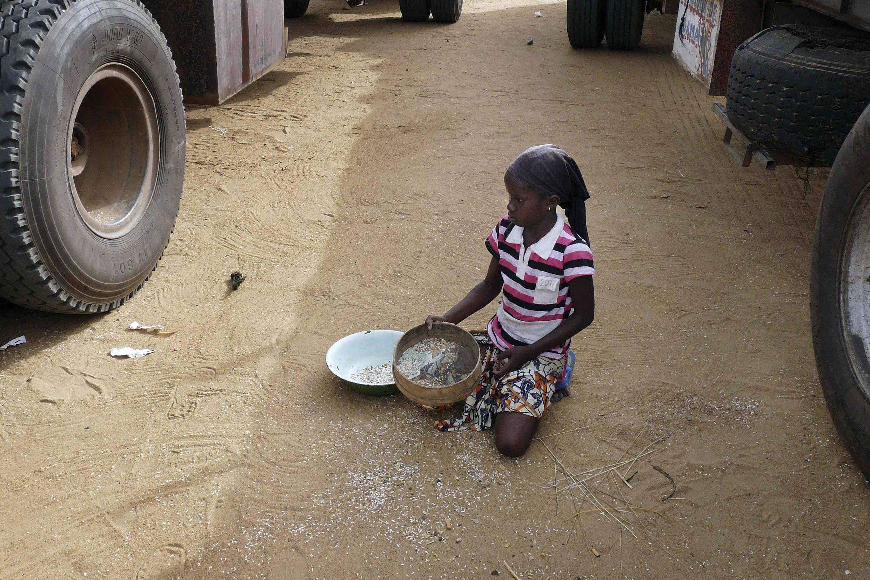 Une petite fille recueille des grains de riz tombés d'un convoi humanitaire, à Gao, le 14 juin 2012.