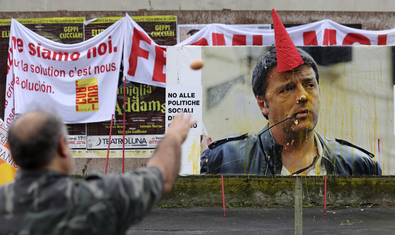 Manifestantes jogam ovos em cartaz do primeiro-ministro Matteo Renzi, que propõe uma flexibilização da legislação trabalhista na Itália.