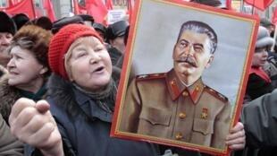 Портрет Сталина в руках участника акции коммунистов в Москве 23 февраля 2010