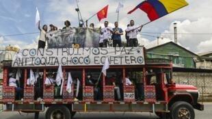"""Les FARC en route pour la capitale à bord de """"chivas"""" ces autobus traditionnels colorés, pour demander l'application des accords de paix de 2016, sur la route entre Medellin et Bogota, le 29 octobre 2020."""