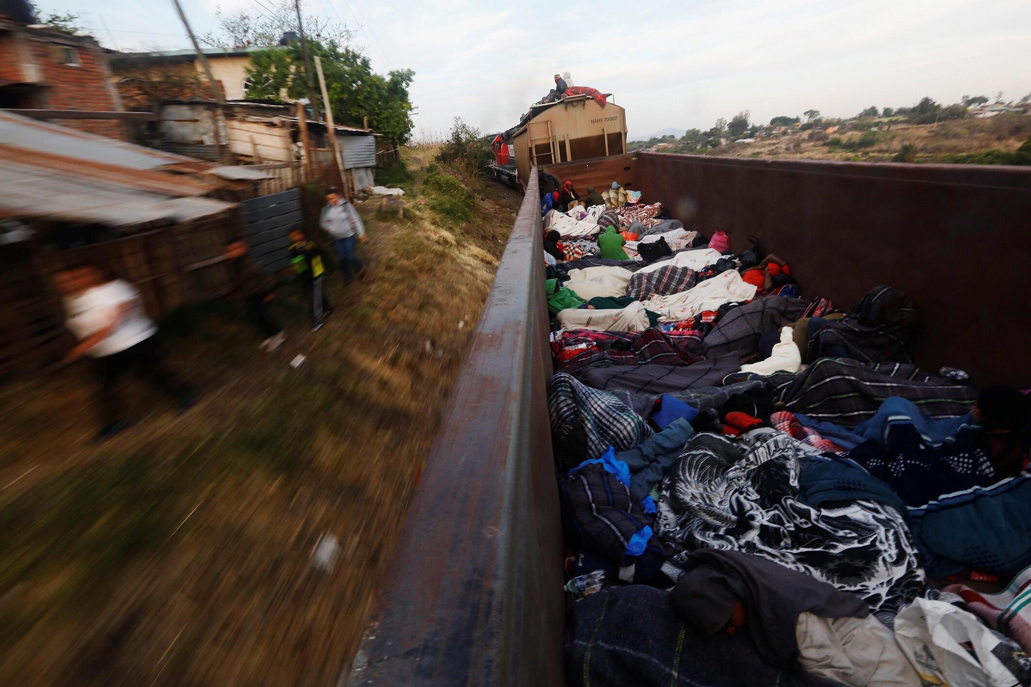 Migrantes centro-americanos atravessam México em trem de carga.